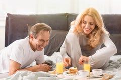 O meio envelheceu os pares que comem panquecas junto na cama fotos de stock royalty free