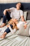 O meio envelheceu os pares que riem e que encontram-se na cama em casa fotos de stock royalty free