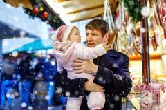 O meio envelheceu o pai que guarda a filha do bebê perto do suporte doce com pão-de-espécie e porcas Família feliz no mercado do  foto de stock royalty free