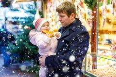 O meio envelheceu o pai que guarda a filha do bebê perto do suporte doce com pão-de-espécie e porcas Família feliz no mercado do  fotos de stock