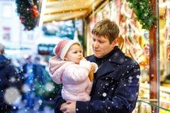 O meio envelheceu o pai que guarda a filha do bebê perto do suporte doce com pão-de-espécie e porcas Família feliz no mercado do  imagem de stock royalty free