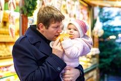 O meio envelheceu o pai que guarda a filha do bebê perto do suporte doce com pão-de-espécie e porcas Família feliz no mercado do  fotografia de stock royalty free