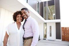 O meio envelheceu o suporte afro-americano dos pares fora de admirar sua casa moderna, vista traseira foto de stock