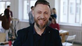 O meio feliz do close-up envelheceu o homem de negócios do chefe no terno formal preto que sorri alegremente na câmera no fundo d vídeos de arquivo
