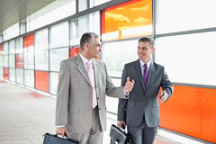 O meio feliz envelheceu os homens de negócios que falam ao andar na estação de estrada de ferro fotos de stock royalty free