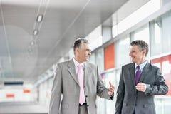 O meio feliz envelheceu os homens de negócios que falam ao andar na estação de estrada de ferro fotos de stock