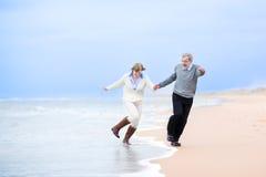 O meio feliz envelheceu os pares que correm em uma praia Imagens de Stock