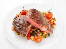 O meio fritou o bife com os vegetais disparados no fundo claro Foto de Stock