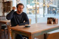 O meio irritado envelheceu o homem caucasiano que senta-se na tabela na cafetaria imagens de stock