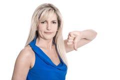 O meio isolado desapontado envelheceu a mulher na camisa azul com polegar imagens de stock