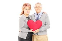 O meio loving envelheceu os pares que guardam um coração vermelho e que olham a came fotografia de stock