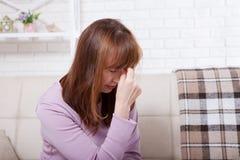 O meio moreno envelheceu a mulher que tem a dor de cabeça no fundo home menopause Copie o espaço fotografia de stock royalty free