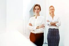 O meio retrato do comprimento de uma fêmea especializada de dois jovens vestiu-se na roupa elegante que levanta na empresa grande Fotos de Stock Royalty Free
