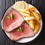 O meio roasted o bife com close-up das batatas em uma placa alto imagem de stock