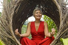 O meio 40s ou 50s atrativo e feliz envelheceu a mulher asi?tica no abrandamento praticando da ioga do vestido vermelho elegante e fotos de stock