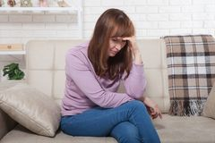 O meio triste envelheceu a mulher que senta-se no sofá e no grito Fundo home Copie o espaço e zombe-o acima imagens de stock