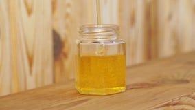 O mel é derramado em um frasco de vidro em um fundo de madeira filme