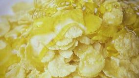 O mel é derramado lentamente em flocos de milho video estoque