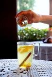 O mel derrama dentro um copo do chá com limão, hortelã e gengibre fotos de stock