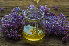O mel orgânico derrama dentro um frasco de vidro, envolvido em uma flor da mola, fotografia de stock royalty free
