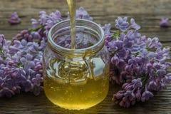 O mel orgânico derrama dentro um frasco de vidro, envolvido em uma flor da mola, fotografia de stock