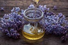 O mel orgânico derrama dentro um frasco de vidro, envolvido em uma flor da mola, foto de stock