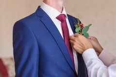 O melhor homem que ajusta o close-up do Boutonniere do noivo Fotografia de Stock Royalty Free