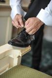 O melhor homem que prepara-se por um dia especial Um noivo que põe sobre sapatas como obtém vestido no vestuário formal Terno do  Fotos de Stock Royalty Free