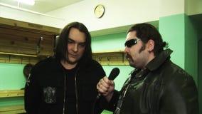 O membro da faixa Kukryniksy Alex Gorshenev dá a entrevista ao homem brutal no casaco de cabedal dos óculos de sol filme