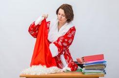 O membro de pessoal de escritório da menina vestido como Santa Claus puxa algo fora do saco para presentes na tabela fotografia de stock royalty free