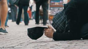 O mendigo desabrigado Man com um chapéu no passeio implora pela esmola dos povos que passam perto vídeos de arquivo