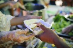 O mendigo está esperando o alimento do auxílio da caridade: o conceito do pedido e da fome: Os problemas da fome dos pobres foram imagem de stock