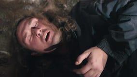 O mendigo sujo, desabrigado come o alimento em uma sala abandonada Homem não barbeado, de cabelos compridos video estoque