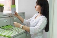 O menina-administrador da clínica médica encontrou na gaveta da cremalheira o cartão paciente desejado e verifica a conformidade  fotografia de stock