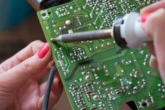 O menina-coordenador repara uma fonte de alimentação do impulso do interruptor A instalação e solda de componentes eletrônicos Foto de Stock Royalty Free