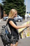 O menina-viajante com um mapa Fotos de Stock Royalty Free