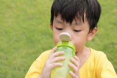 O menino é água potável de sua garrafa no parque fotos de stock