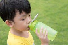 O menino é água potável de sua garrafa no parque imagens de stock