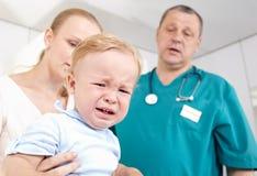 O menino é amedrontado e de grito em um estudo médico. Fotos de Stock