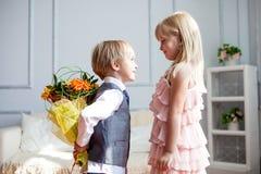 O menino é apresentado flores à menina fotos de stock royalty free