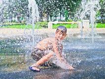 O menino é banhado na fonte Imagens de Stock