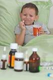 O menino é doente Guardando um comprimido e não queira bebê-lo imagens de stock