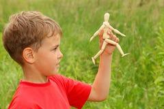 O menino é jogado pelo manequim pequeno de madeira Imagem de Stock