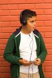 O menino é música de escuta com Smartphone Imagens de Stock Royalty Free