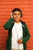 O menino é música de escuta com Smartphone Foto de Stock