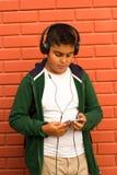 O menino é música de escuta com Smartphone Foto de Stock Royalty Free