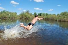 O menino é mergulhos banhados, salta no rio Foto de Stock