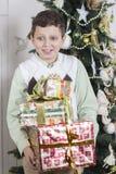 O menino é oprimido com muitos presentes do Natal Fotos de Stock