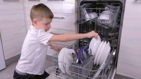 O menino é pôr pratos na máquina de lavar louça na cozinha vídeos de arquivo