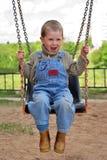 O menino é playng nos balanços Imagens de Stock Royalty Free